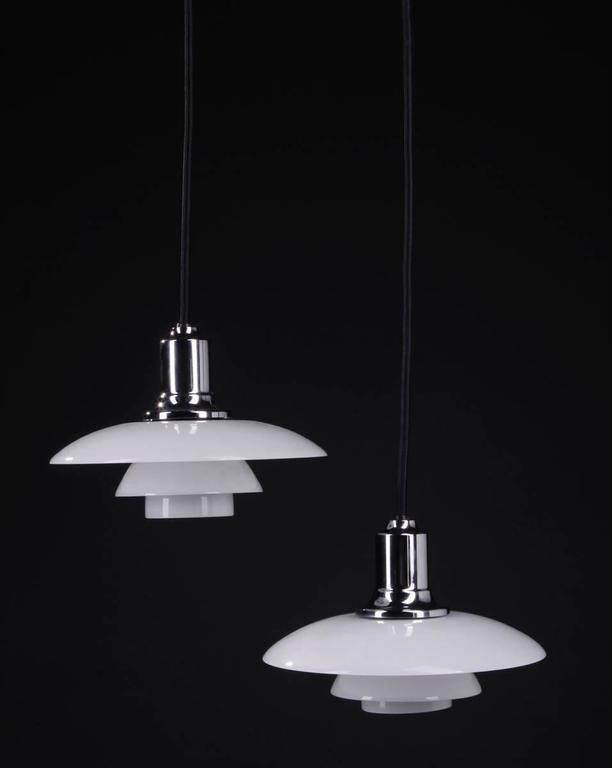Poul Henningsen PH 2/1 pendants.  Fitted with one E27 socket, white opal glass shades, black fabric cords.  Produced by Louis Poulsen. Ø 20 cm. Minimal wear.