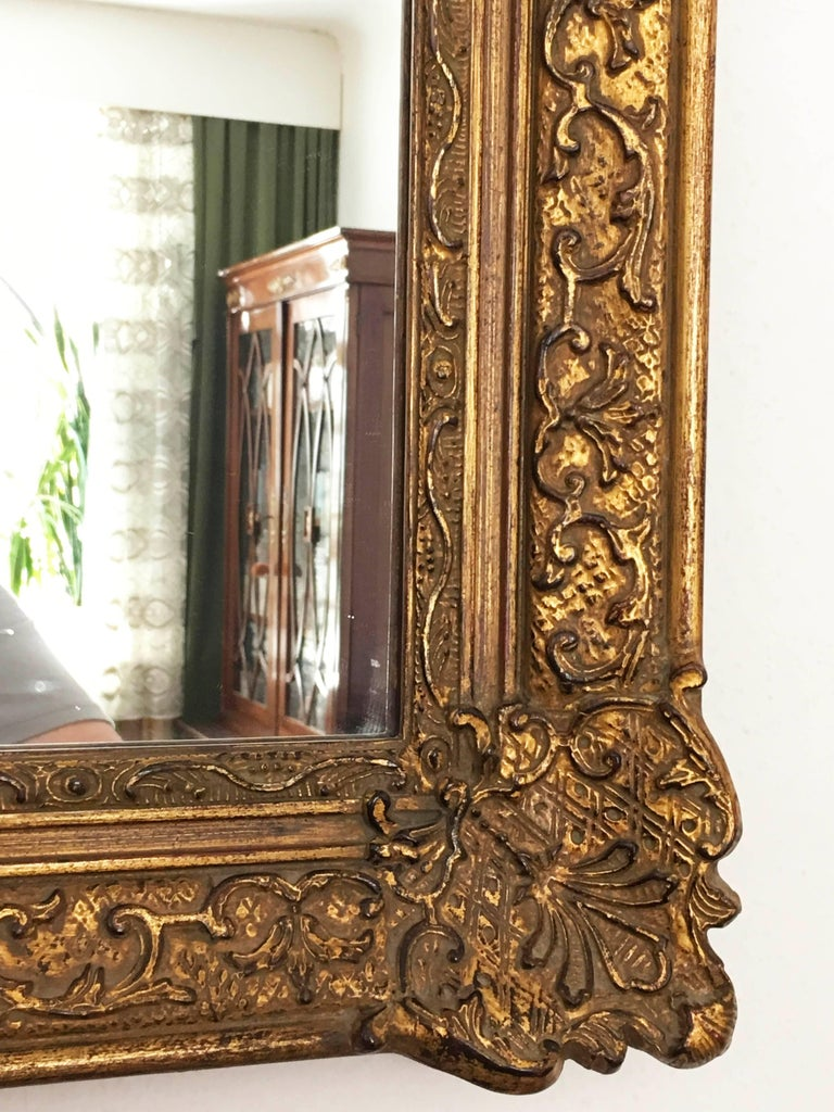 Made in early 20th in Baroque style giltwood carved mirror, the shaped frame carved with floral motifs, leaves, flowers. Water gilding of polished and matte quality, with some bleeding of the bole, the mirror plate recent replacement.