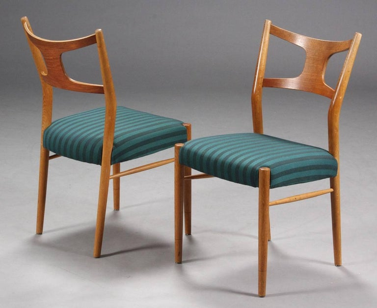 Kurt Østervig, solid dining chairs made of oak and teak, seats upholstered. Designed in 1956. Produced by Randers Furniture. A very good original condition, new upholstery and wood renovation possible on request. Up to ten chairs and 2 armchairs
