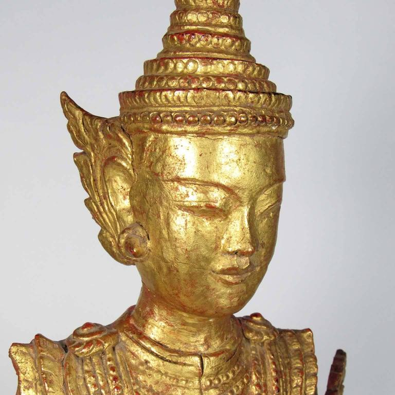 A gilt wooden figure of a standing Buddha, late 19th century, Thailand. Measures: Height 35 in. (88.9 cm), width 12 in. (30.48 cm), depth 8 1/2 in. (21.59 cm).