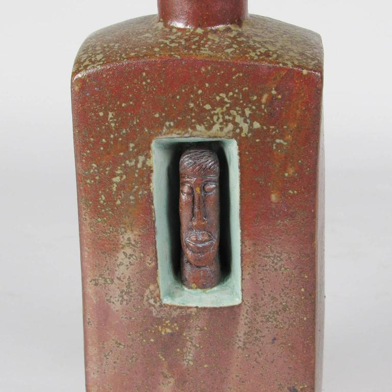 Unusual American arts and crafts glazed ceramic flask, early 20th century; with face form mask decoration. Iron red glaze with turquoise glaze reserve and neck, marked