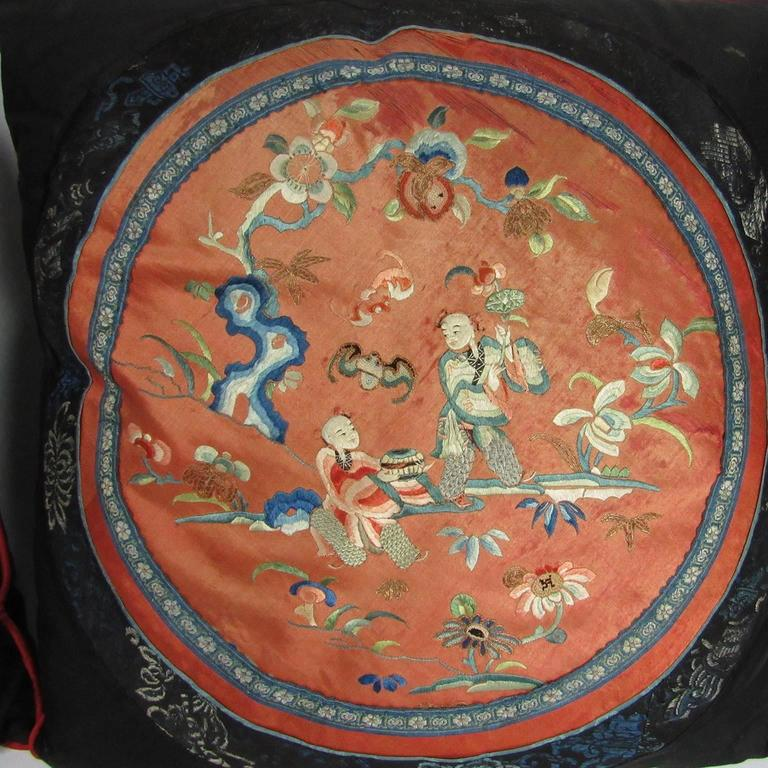 Two 19th century Chinese silk embroidered textiles fashioned as pillows with black fabric backing. One with figuresand horse in a blue ground landscape. The other with two figures in a salmon ground landscape with flowers and vines. Measures: 16 x