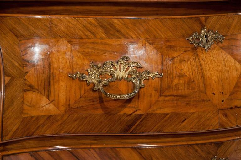 A stunning Swedish 19th century walnut bombe shaped chest of drawers with ormolu mounts. Of fantastic colour and design this antique Swedish chest of drawers dates to circa 1860 having a serpentine shaped top with decorative parquetry style walnut