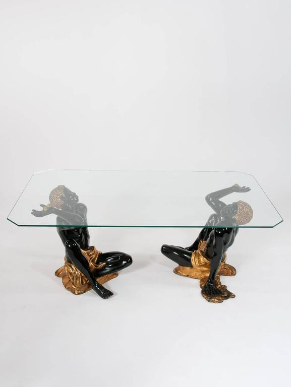 A fabulous and rare pair of blackamoors supporting a later glass top.