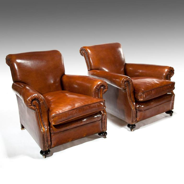 A Fine Pair Of Antique Leather Club Chairs Raised On Turned Front Bun Feet  And Of