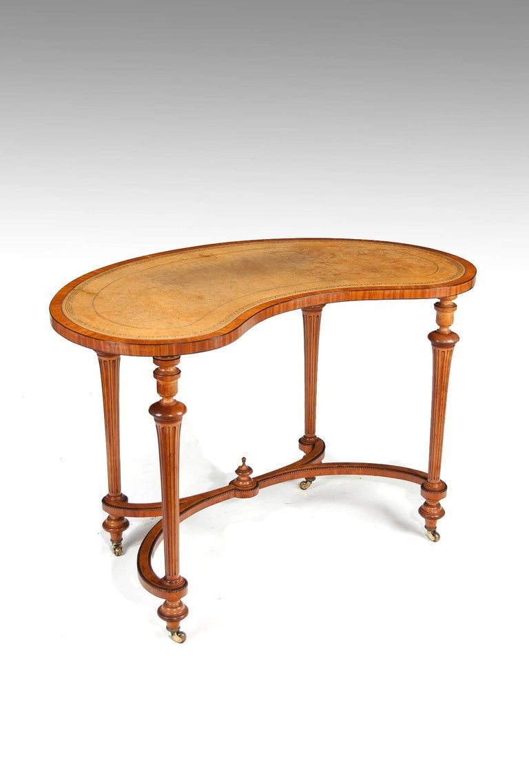 A very fine satinwood and ebony inlaid mid-19th century kidney shaped writing table side table in the manner of Gillows.