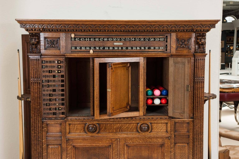 A late 19th century carved oak billiards cabinet by Thurston & Co. of London.  For the games of Billiards, Pool and Snooker.  The centre panel revolves to reveal snooker scorer. The centre panelled door has a revolving panel revealing a slate