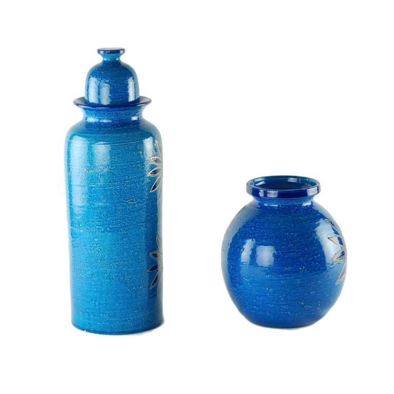 This ceramic vase and lidded jar were designed by Aldo Londi, art director for Bitossi ceramiche in Montelupo, Italy. Both pieces feature large stylized flowers and have been finished in Bitossi's rich Rimini blu glaze reminiscent of the Adriatic.
