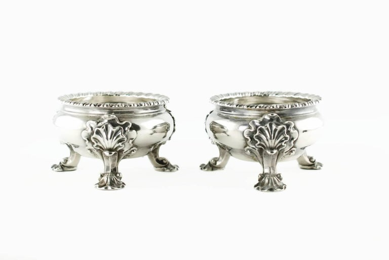This substantial pair of English sterling silver master salts were made in 1741-1742 during the reign of King George II by London silversmith Lewis Pantin I. The bowls have a gadroon edge and rest on three ornate shell form feet. The set displays
