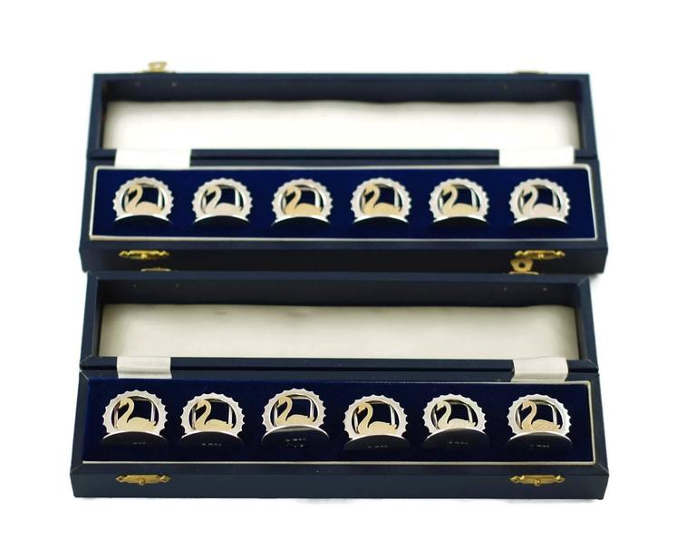 This elegant set of 12 sterling silver menu place card holders was made by Asprey of London. The pieces have circular bases surmounted with arched menu place card supports and feature swans in profile which have been accented in vermeil. The swans