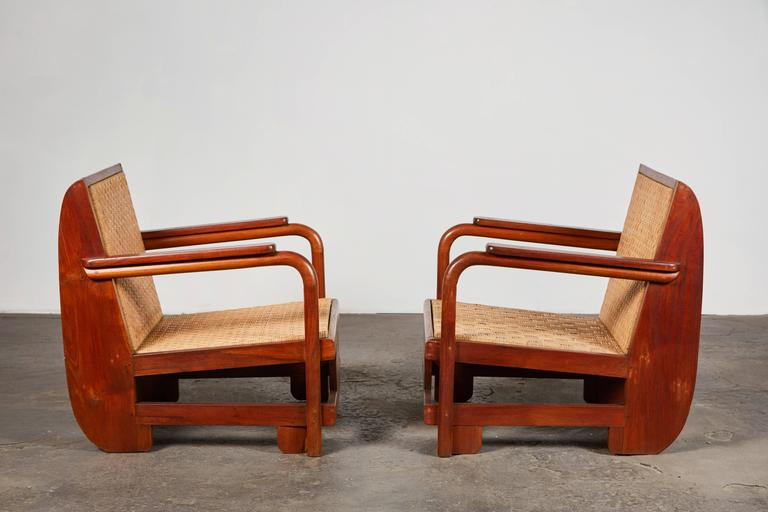 Pair of sculptural wood armchairs with woven cane seat and backrest. Made in USA, circa 1930s.
