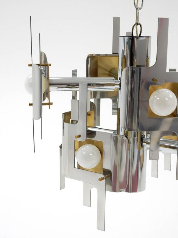 Fantastic sculptural brass, chrome and polished aluminum chandelier designed by Gaetano Sciolari. Eight white