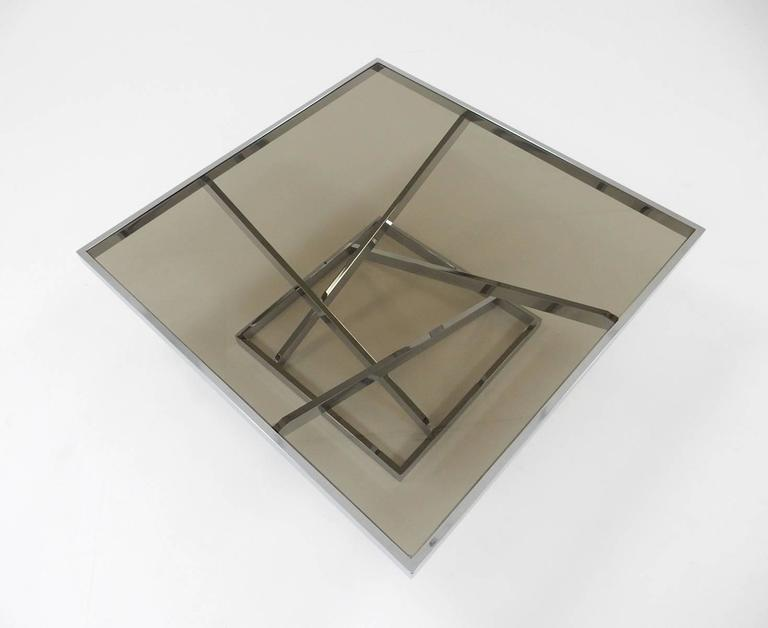 Large architectural design chrome flat bar steel coffee table with smoke glass top by Design Institute of American in the style of Milo Baughman, circa 1970s. This table is solid and in excellent condition except for a chip in two corners of glass