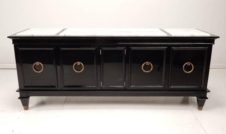Incredible low storage cabinet with mirrored black lacquer finish and three-part white marble inlay top. Four-door cabinet each with solid brass ring pull. Capped brass feet. Finished back.