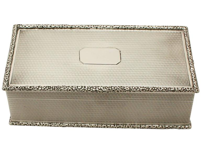 An exceptional, fine and impressive antique George V English sterling silver cigarette or cigar box; an addition to the ornamental silverware collection.  This exceptional antique George V sterling silver cigarette box has a plain rectangular
