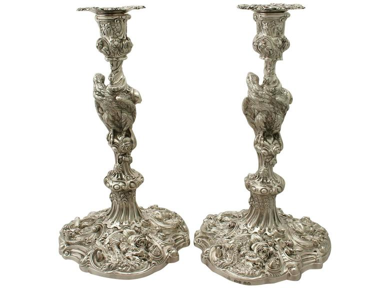 A magnificent, fine impressive pair of antique George IV English cast sterling silver candlesticks made by Robert Garrard II; an addition of our ornamental silverware collection.  These magnificent antique George IV cast silver candlesticks, in