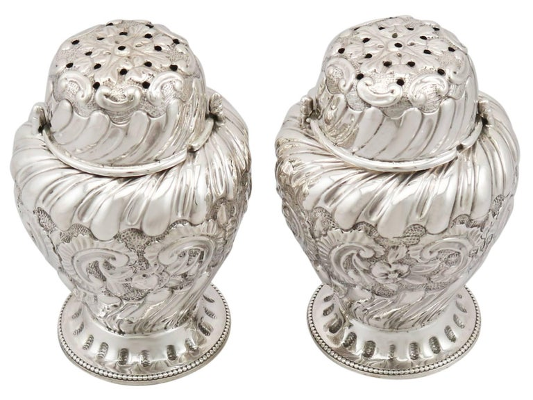 A fine and impressive pair of antique Victorian English sterling silver condiment shakers; an addition to our silver tableware collection  These impressive antique Victorian English sterling silver condiment shakers have an inverted pear shaped