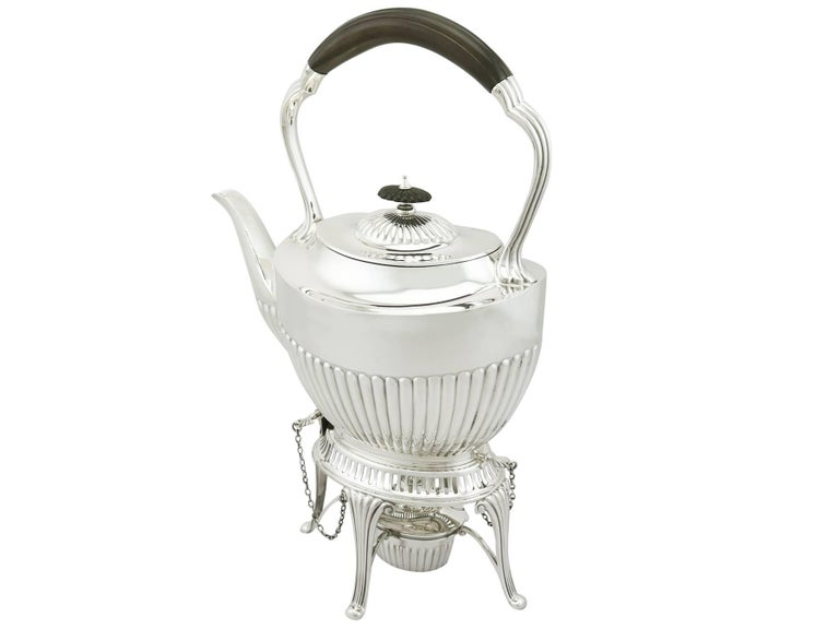 An exceptional, fine and impressive antique Edwardian English sterling silver spirit tea kettle made in the Queen Anne style; an addition to our antique silver teaware collection.  This exceptional antique Edwardian silver spirit kettle, in