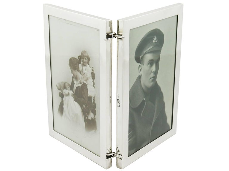 An exceptional, fine and impressive antique George V sterling silver double photograph frame; an addition to our ornamental silverware collection.  This exceptional antique George V sterling silver double photo frame has a plain rectangular form