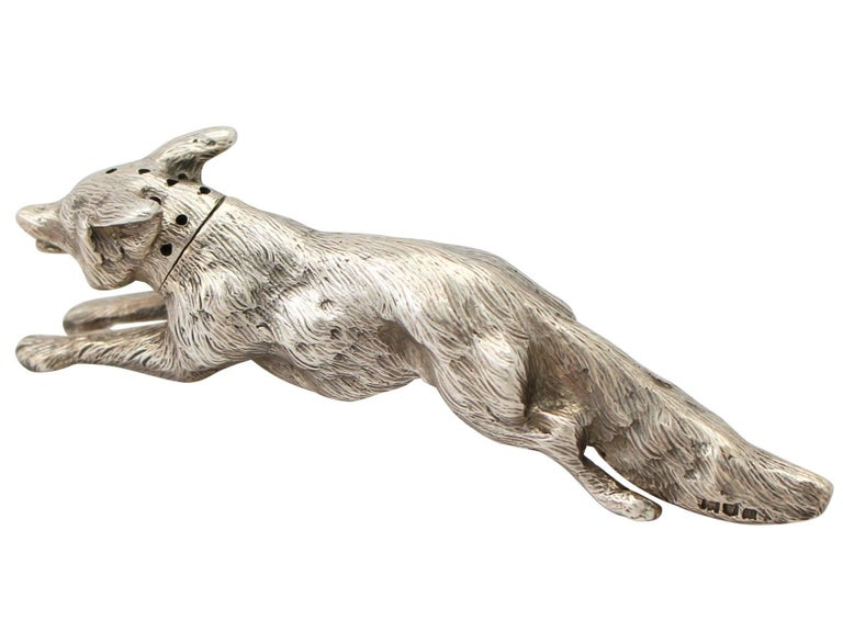 An exceptional, fine and impressive antique George V English cast sterling silver pepperette in the form of a fox; an addition to our animal related silverware collection.  This exceptional antique George V cast sterling silver pepperette has been