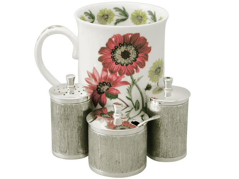This fine vintage Elizabeth II English sterling silver three-piece condiment set consists of a salt pot, a pepper pot and a mustard pot.  Each piece has a cylindrical form onto a collet shaped foot.  The surface of each piece is embellished with