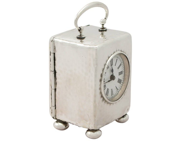 A fine and impressive antique Victorian English sterling silver eight-day boudoir clock; an addition to our silver timepiece collection.  This fine antique Victorian sterling silver boudoir clock has a plain rectangular form onto four bun
