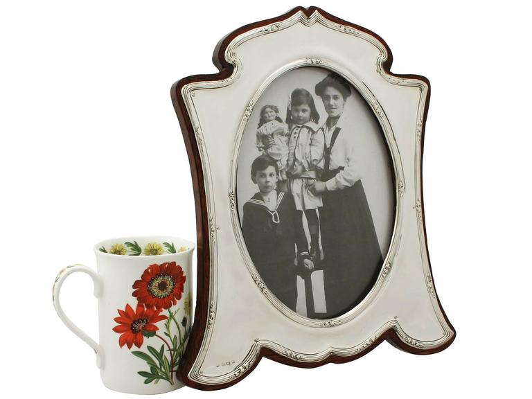 A fine and impressive, large antique George V English sterling silver photograph frame; an addition to our ornamental silverware collection.  This fine antique George V sterling silver photograph frame has a waisted arabesque style shaped form