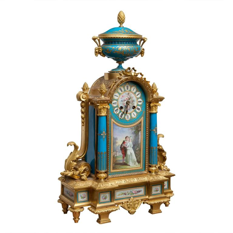 France, circa 1870.  A fine late 19th century ormolu and porcelain mounted mantel clock, the painted dial above a courting couple scene, the whole mounted with a Krater vase and raised on a stepped porcelain mounted base.   The clock is 54cm