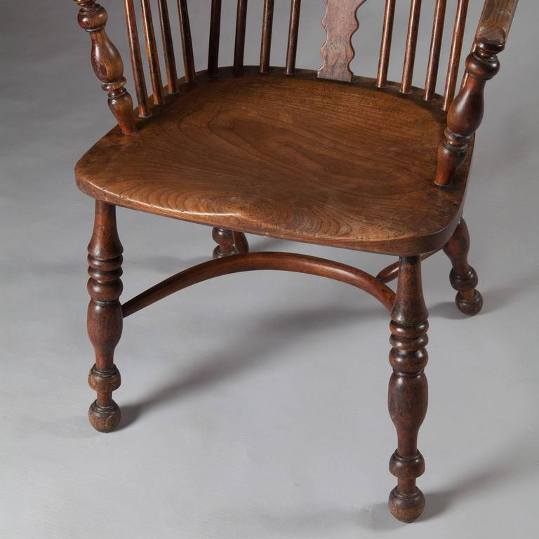 Early 19th century Yew-wood Windsor armchair with crinoline stretcher, well figured.  Measures: Height 118cm. Width 63cm. Depth 54cm. Seat Height 46cm.  The Windsor chair is established as one of the great classics of English country