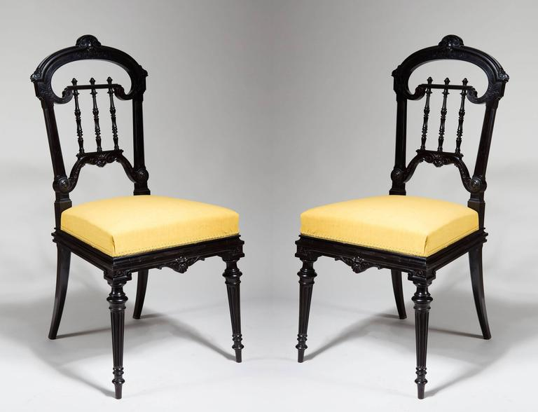 A pair of 19th century solid ebony chairs carved through in low relief with foliate decoration. The back splat fashioned as delicately turned spindles. Standing on turned legs at the front and sabre ones at the back.  The blocks underneath with