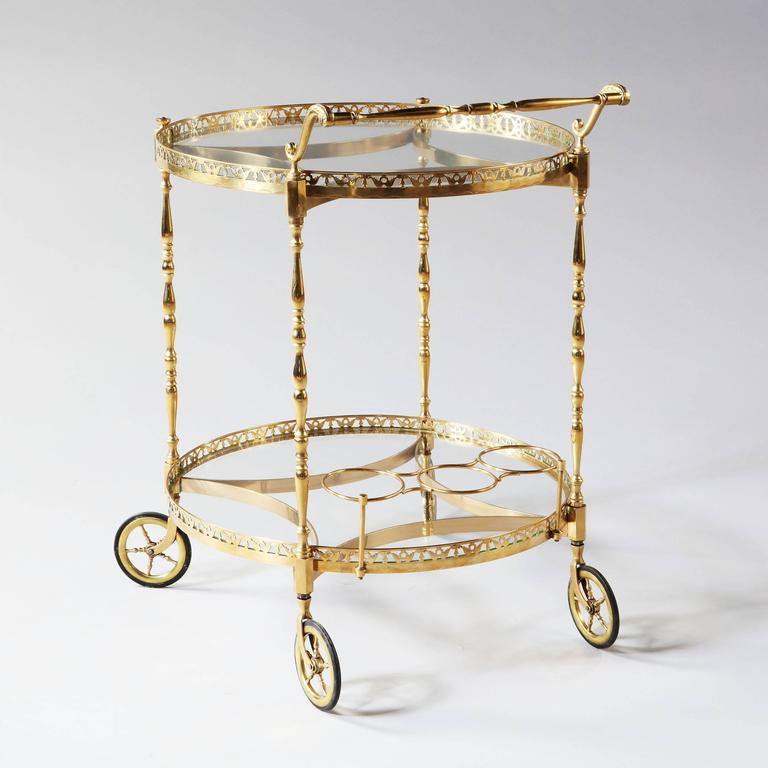 Fabulous and very fine circular polished brass bar cart with two levels, the borders of pierced brass supported on turned brass legs with concave stretchers, an ornate handle and raised on four brass wheels. 