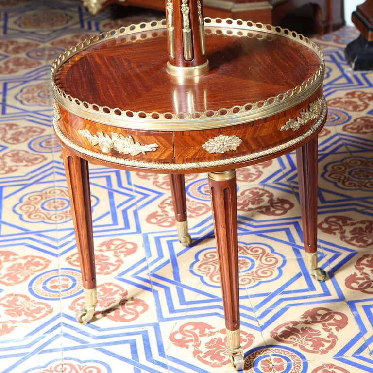 A near pair of two tier circular end tables with pierced galleries, book matched veneers and raised on tapering fluted legs with castors. the gilt bronze mounts throughout of exceptional quality.  France circa 1900  Height 81 & 78 cm Diameter 41cm