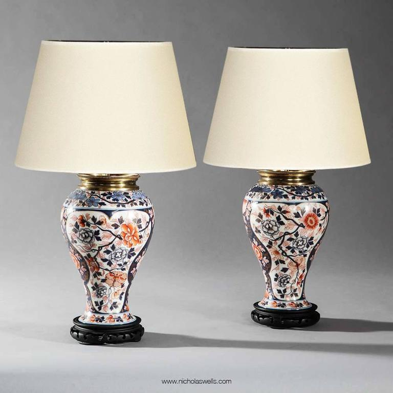 Pair of Imari pattern Bayeux, Veuve Langlois porcelain oil lamps, France. Each of baluster form, decorated with flowers and foliage in polychrome colours of blue, coral and orange on a white ground with gold leaf detailing and fitted with original