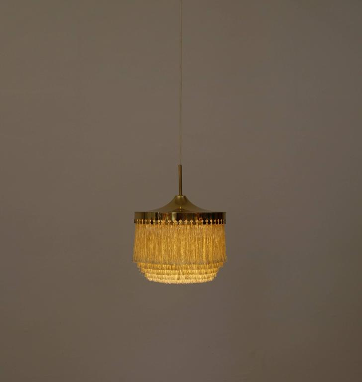 Champagne colored silk fringes pendant light with brass frame. Great original condition. Fitted with one E27 socket.  Measures: Height of the lamp only from bottom of fringes to top of brass crown approximately 36 cm, wire length 120-130