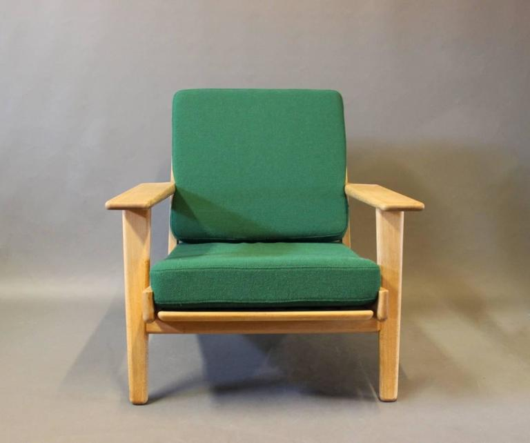 Armchair, model GE290, designed by Hans J. Wegner in the 1950s and manufactured by GETAMA in the 1960s. The chair is of oak and with cushions upholstered in dark green Hallingdal wool.