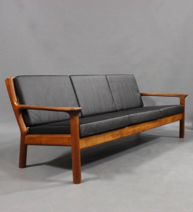 Three-seat sofa in teak and cushions of black leather designed by Juul Kristensen and manufactured by Glostrup Furniture Factory and of Danish design from the 1960s.