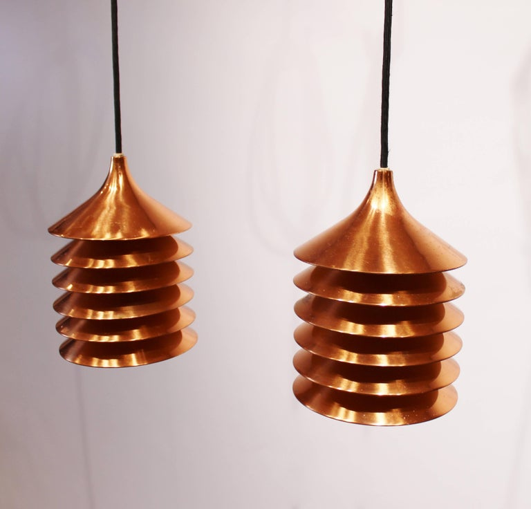 A pair of copper pendants of Danish design from the 1960s. The pendants are in great vintage condition with new black fabric cord.