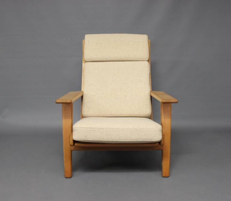 Armchair with high back, model GE290A, designed by Hans J. Wegner in the 1950s and manufactured by GETAMA in the 1960s. The chair is made of oak and cushions in light hallindal wool.