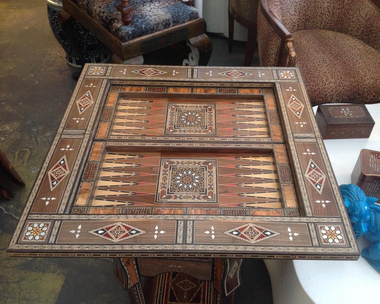 The console form table (when closed) unfolds to reveal a backgammon board. A removable chess board can be inserted; or its reverse felt covered top can be  utilized for cards. The table is as versatile as it is beautiful with thousands of  inlaid