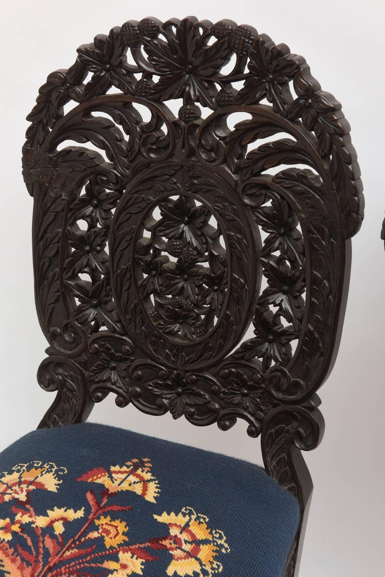An exceptional and rare set  with superior and intricate leaf and berry carving. Unusual form and style. The chairs are priced as pairs. Price is for one pair only.