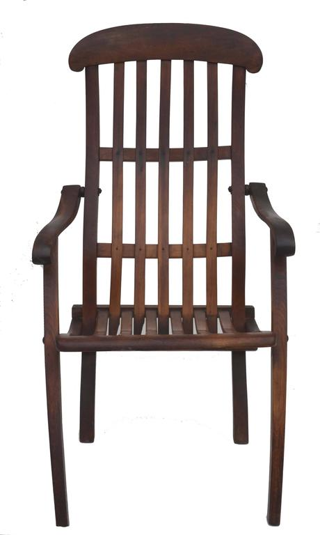"""Wonderful dark teak antique folding deck lounge chair. Original hardware and finish. Very comfortable and cushion not necessary. circa 1900. Condition and wear consistent with age. folds for storage and convenience. Size 38"""" H x 38"""" W."""