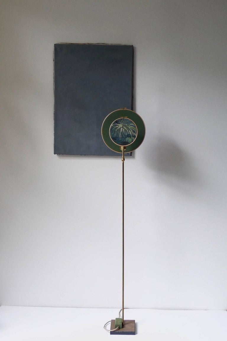 Light object, floor lamp, circle blue grey Handmade in brass, leather, wood and hand printed and painted linen. A dimmer is inlaid with leather Dimensions: H 130 x W 27 x D 16 cm The design artwork is meticulously handcrafted in a limited