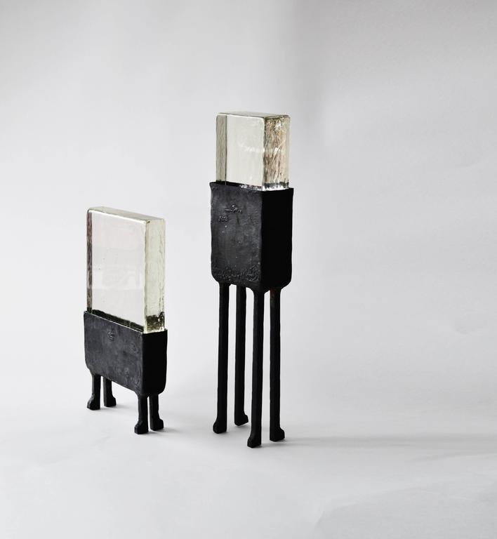 Cast glass and blackened steel are combined to become a striking table lamp. Unusual geometries and heavy material textures make this lamp very special and one of a kind.  Materials: Blackened steel, cast glass, led lighting  Dimensions: 20