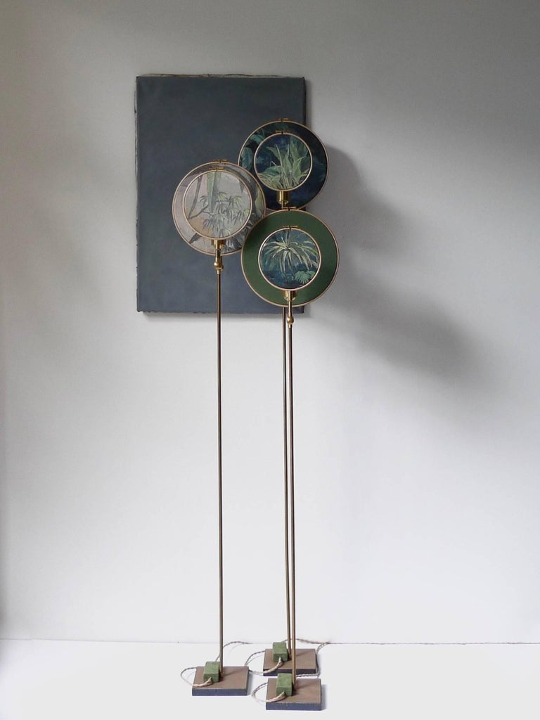 Light object, floor lamp, circle blue grey Handmade in brass, leather, wood and hand printed and painted linen. A dimmer is inlaid with leather Dimensions: H 160 x W 27 x D 16 cm The design artwork is meticulously handcrafted in a limited