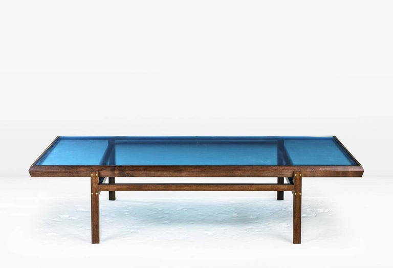 The Pintor Coffee Table's solid wood frame with Brass inlay is engineered with chamfered edges to provide a simple but worthy setting for the jewel toned, colored glass which forms the tabletop. Shown with solid American Black Walnut frame and Ice