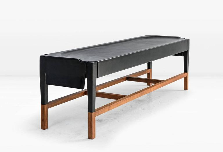 The centuries old process of forming water saturated leather hide over a wood frame forms the essence of the Cassius bench, which is then exposed at the base to reveal co-planar, walnut legs. Shown in black leather with a solid American black walnut