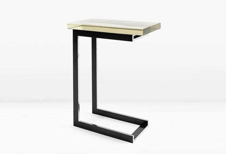 The Dempsey side table can easily assimilate into any room by Virtue of both its elegant minimalism and its petite size. Shown with a 1 3/8 inch thick silvered Borosilicate glass top and deeply patinated, Nickel base which is polished along one edge
