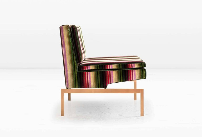 The Mancini chair has a seat specially constructed to float above the metal base. The semi-attached seat and back cushions afford an extra layer of comfort. Shown with a solid silicon bronze base and striped velvet. Also available with a nickel