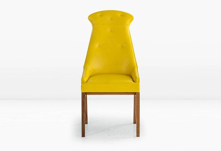 The Evander has a sleek, attenuated form yet somehow manages an enveloping comfort. Upholstered seat and back on a solid wood base. Shown with American black walnut base and Daffodil Leather. Last image shown in olive leather. Also available with a