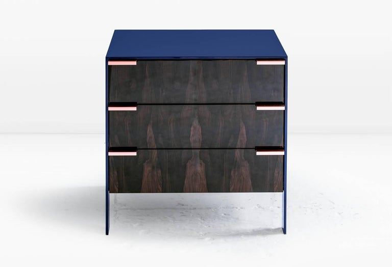The Johansson cabinet / end table has a skin of 1/2 inch lacquered aluminum encasing a cabinet constructed of highly polished wood veneer exteriors and solid wood interiors. Doors have solid metal pulls. Like all KGBL cabinetry, this piece is